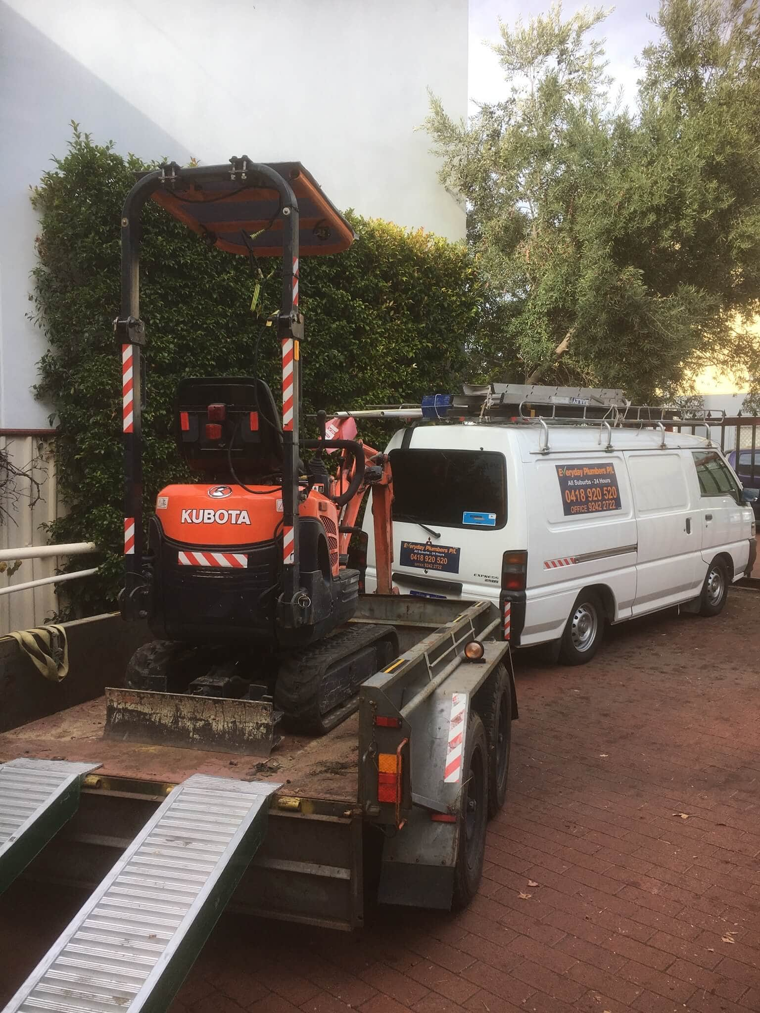 Everyday Plumbers Residential Locating Burst Pipes - Backhoe in the Trailer Service Unloading 2025